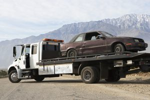 Picture of damaged car being hauled on RamblingWrecker-Manassas flatbed truck.