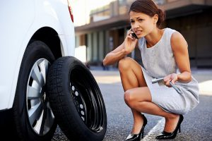 Picture of woman on phone with the Rambling Wrecker-Manassas seeking help for a flat tire