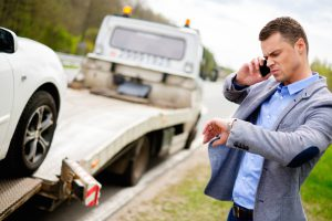 Picture of man talking on the phone and looking at watch while car is towed